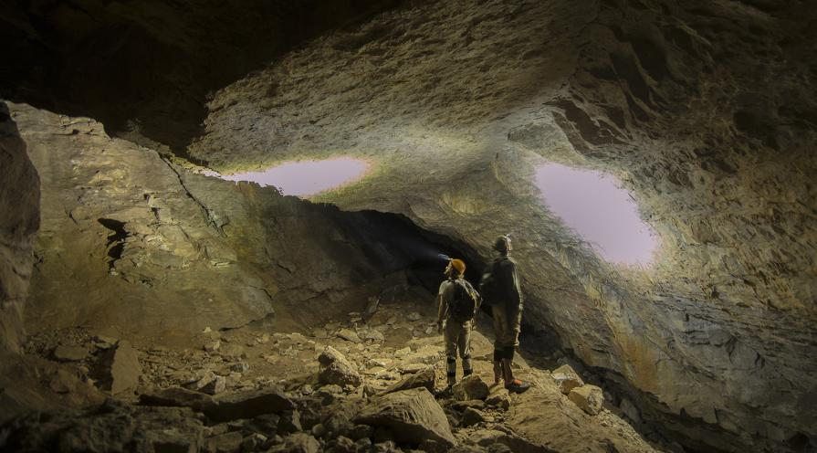 Two men shine their headlamps up at the ceiling of Bloomington Cave.
