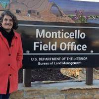 lady in red coat standing in front of Monticello FO sign