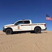 A law enforcement truck with an American flag parked on a sand dune