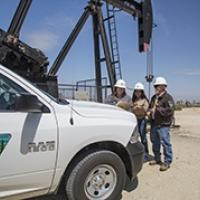 BLM workers in front of a pump jack.