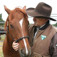 A man wearing a cowboy hat tenderly looking at a horse he is embracing.