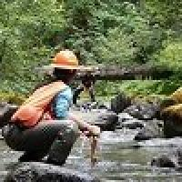 Two BLM employees conduct scientific research in a stream