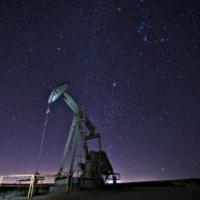 A pump jack against a starry night sky.