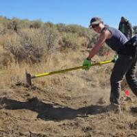 A volunteer clears an trail with a hoe.  Photo by Stan Bales, BLM.