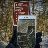 person holding smart phone with georeferenced map opened up in mobile app with trail and trail signage in the background during winter at Campbell Tract