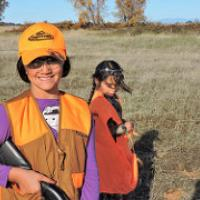 Two girls wear bright vests while learning to hunt on public lands. (Eric Coulter/BLM)