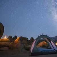 An open tent under a starry sky.