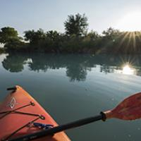 The view from a red kayak on a calm river at sunrise.