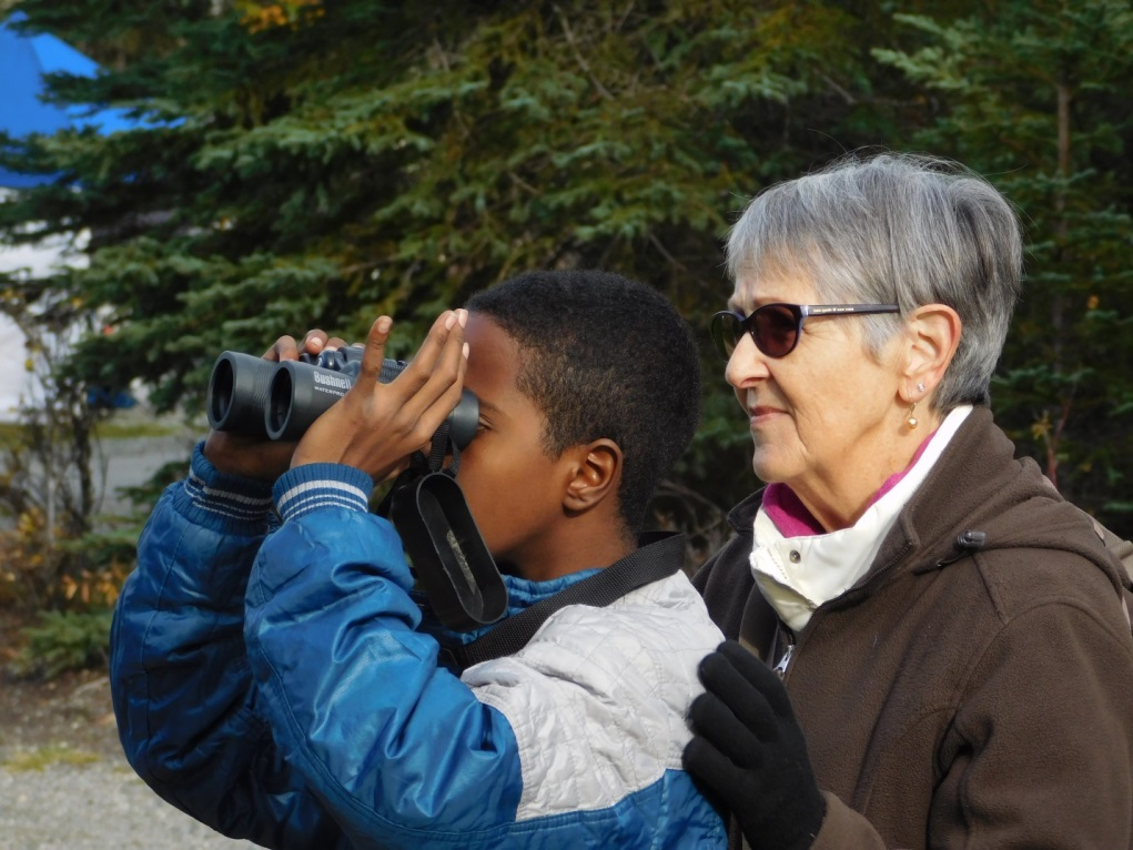 A member of the Alaska Audubon Society shows a visitor how to spot for binoculars.