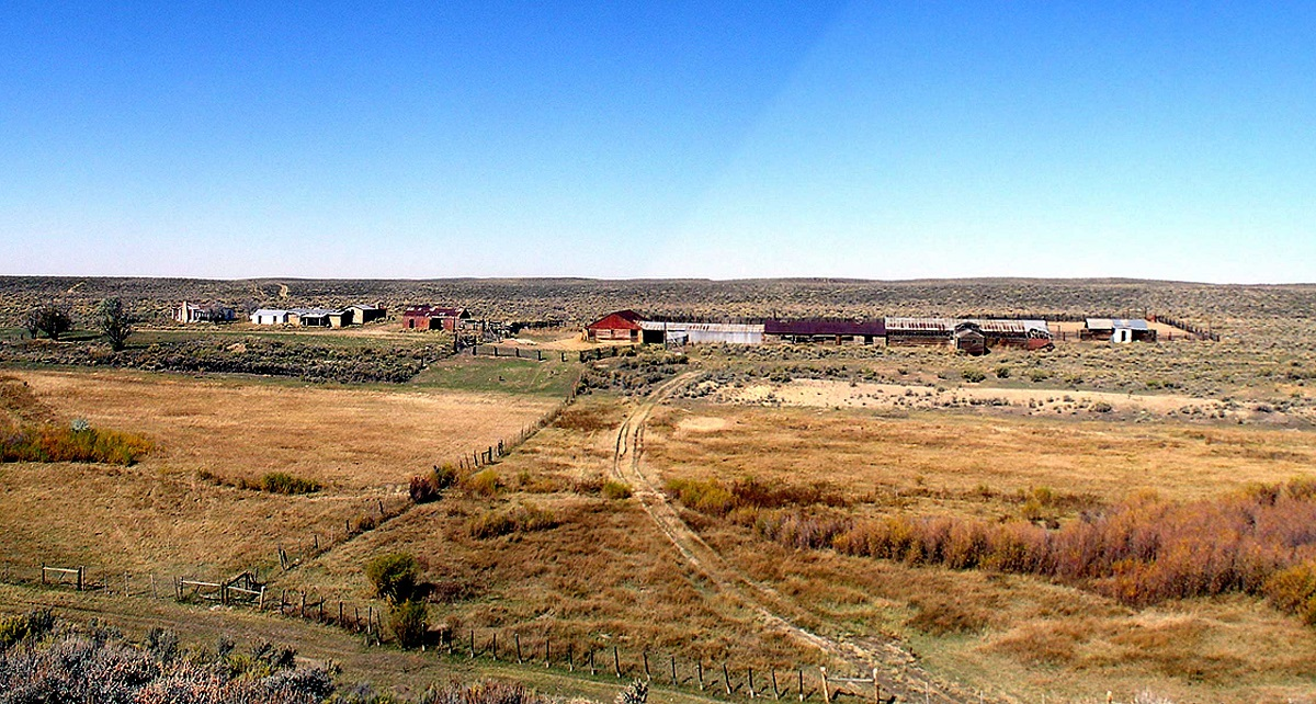 A distance view of about a dozen old ranch buildings surrounded by prairie.