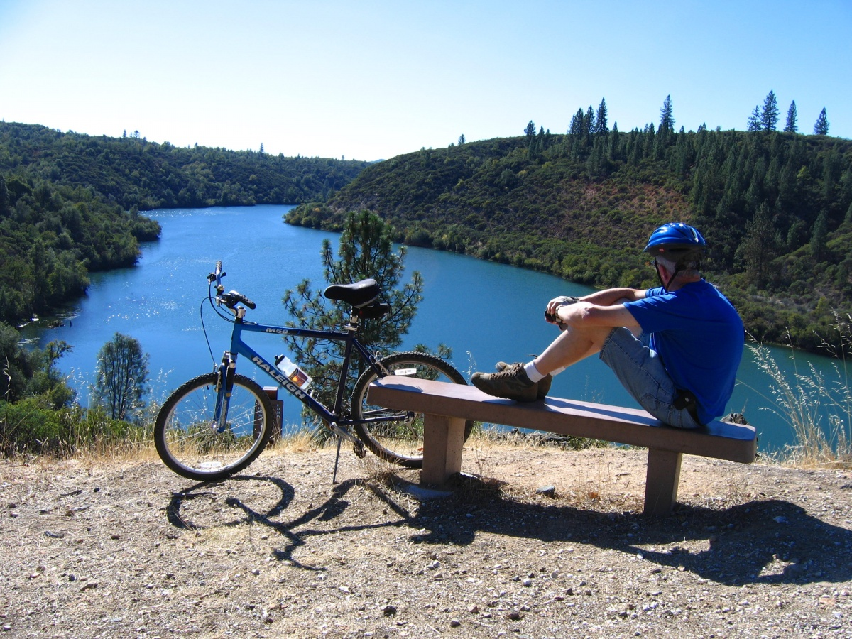 A bicycle rider takes a break on a bench at a river overlook.