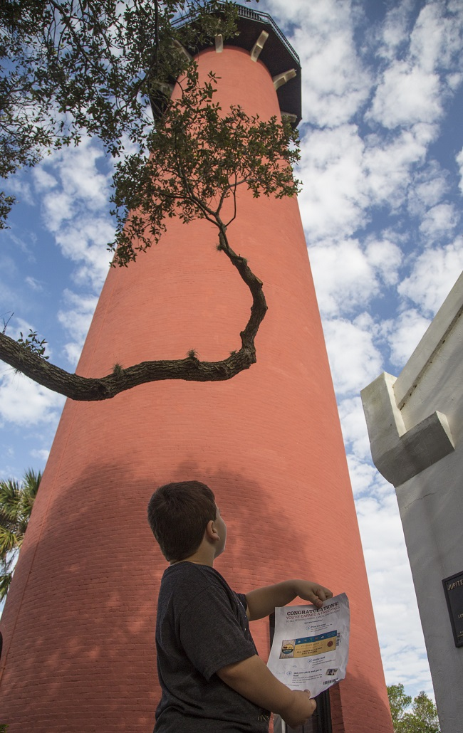 A child viewing Junior Ranger materials in front of the Jupiter Inlet Lighthouse.