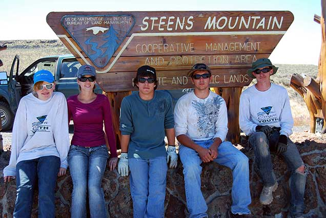 Five individuals in sunglasses and hats sit on a stone wall in front of a sign for Steens Mountain Cooperative Management Area.