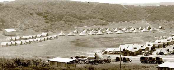 Historic picture of Fort Ord Army Base.  The picture is sepia colored.  In the foreground there is a small wooden building. Old vehicles are parked along a small road. In the background are rows of tents pitched in rows before a small hill.