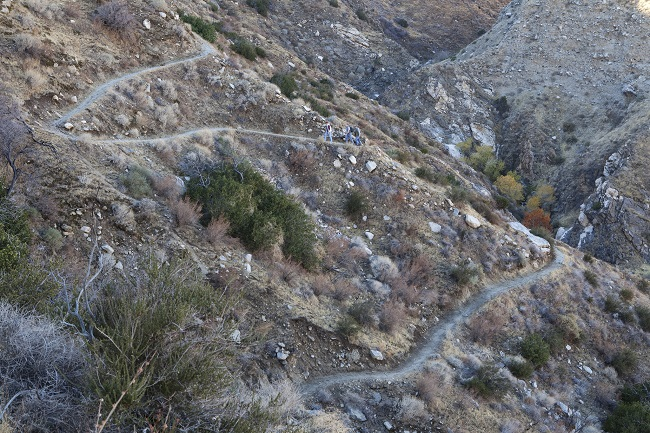A group of hikers on the Pacific Crest Trail climb a steep grade in a rocky area. Photo by Bob Wick.