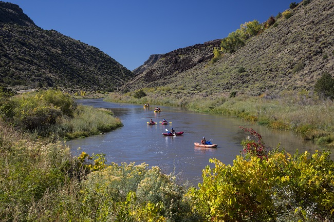 Boaters on the Rio Grande Wild and Scenic River in New Mexico enjoying the flowers and scenery.