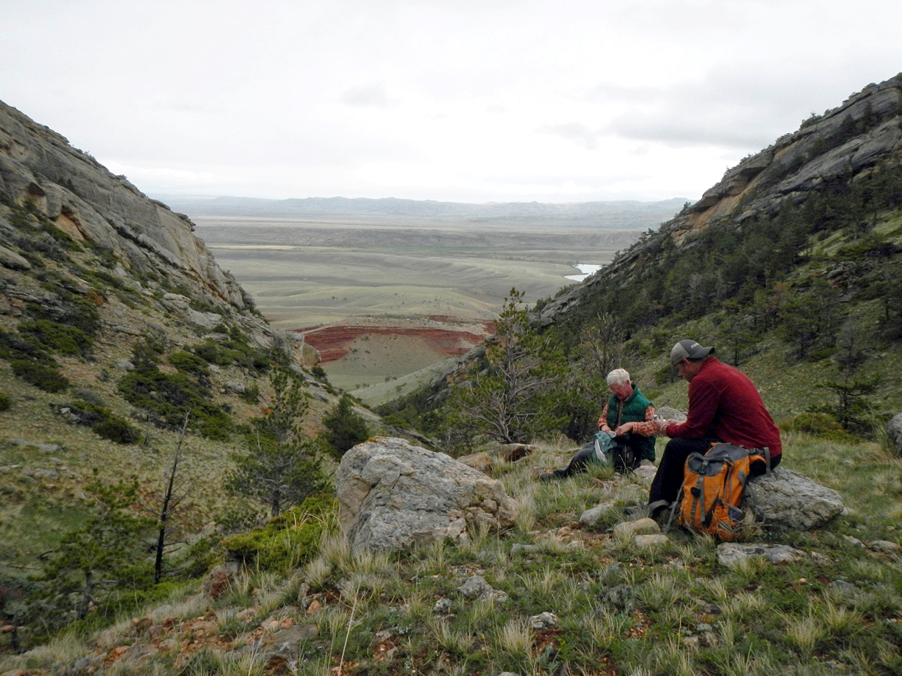 Two hikers with back packs on top of a large hill overlooking a big valley.